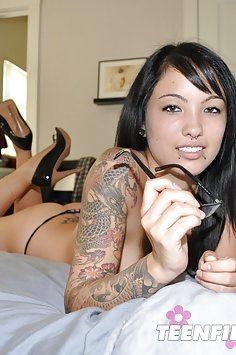 Asian mixed race geek girl shows tattoos and piercings